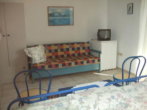 Die Schlafcouch, der Kühlschrank und der Fernseher des blauen Zimmers.