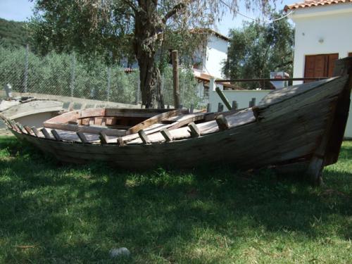 Das Wrack eines alten Fischerbootes in einem Vorgarten.