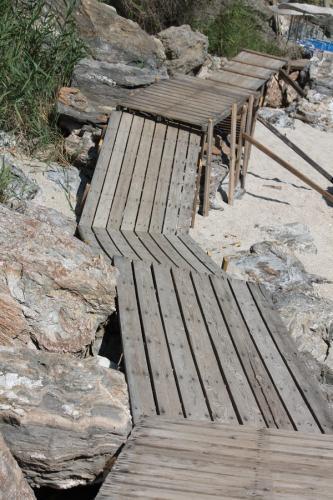 Hinter dem kleinen Hafen von Agios Ioannis führt dieser Brettersteg zum benachbarten Sandstrand.