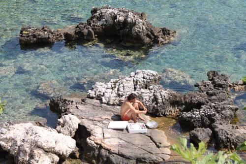 Der junge Mann auf dem Bild macht gerade Gavros sauber und versucht mit den Fischresten einen Oktopus anzulocken.